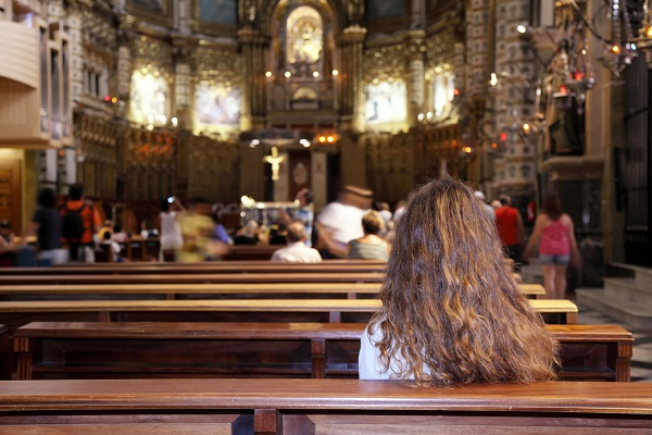 Young woman praying in the church, Montserrat, Spain.